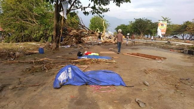 Berbagai bangunan hancur dan jalan retak akibat gempa dan tsunami ini. (AFP PHOTO / OLA GONDRONK)