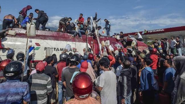 Warga mengambil BBM dari mobil tangki di SPBU, Palu, Sulawesi Tengah. Gempa dan tsunami yang melanda wilayah Palu mengakibatkan kesulitan BBM. ANTARA FOTO/Muhammad Adimaja