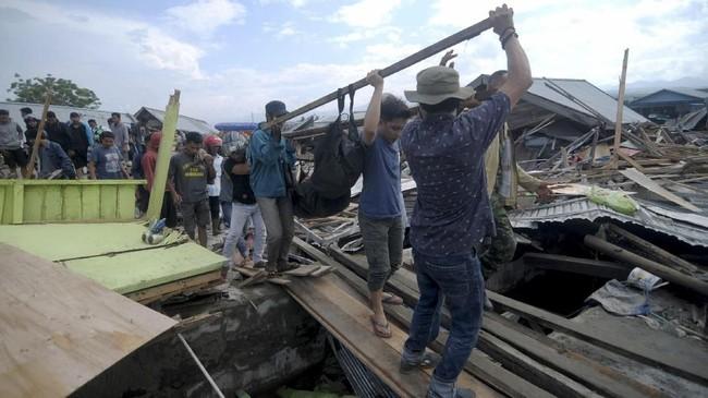 Warga bahu membahu mengevakuasi secara mandiri korban gempa di Palu dan Donggala. Akses yang putus menuju Palu dan Donggala membuat bantuan sulit dikirim. (AFP PHOTO/OLA GONDRONK)
