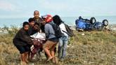 Warga bersama-sama membawa korban gempa sesaar setelah gempa melanda di Palu dan Donggala. (AFP PHOTO / MUHAMMAD RIFKI)