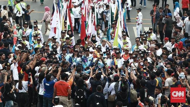 Wakil ketua KPK Laode M. Syarief menerima estafet obor api Asian para Games di kawasan Jalan M.H Thamrin. Jakarta menjadi kota terakhir dari rangkaian pawai obor pesta olahraga disabilitas terbesar se-Asia ini. (CNN Indonesia/Andry Novelino)
