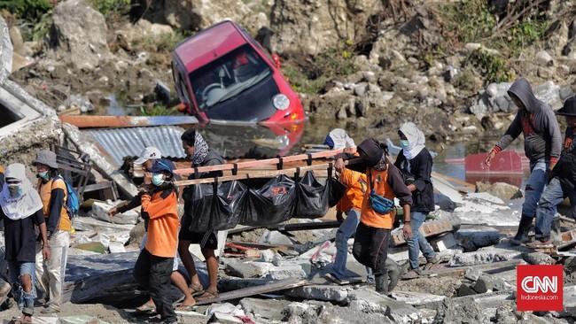 Tim Basarnas bersama warga mengevakuasi beberapa korban gempa yang masih terjebak reruntuhan puing bangunan di Balaroa. Banyak korban yang terjebak di kubangan dan reruntuhan sehingga sukar dievakuasi. (CNN Indonesia/Adhi Wicaksono)