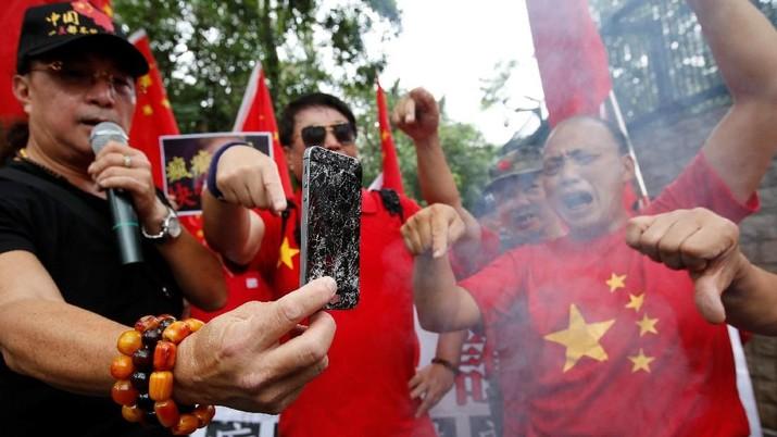 Perang dagang Amerika Serikat dan China memicu protes dan pembakaran iPhone di depan kedutaan AS di Hong Kong.