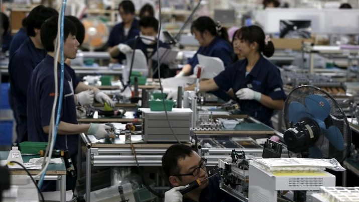 FILE PHOTO: Employees work an assembly line at a factory of Glory Ltd., a manufacturer of automatic change dispensers, in Kazo, north of Tokyo, Japan, July 1, 2015. REUTERS/Issei Kato/File Photo