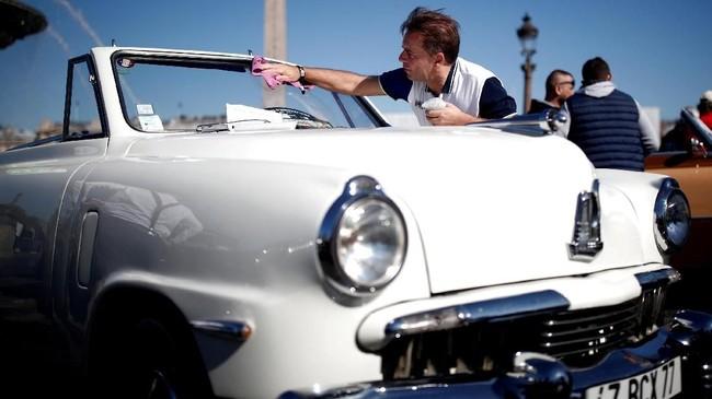 Seseorang membersihkan kaca depan mobil Studebaker cabriolet dalam parade Place de la Concorde yang merupakan bagian dari pameran otomotif Paris Motor Show ke-120 di Paris, Prancis. (REUTERS/Benoit Tessier)