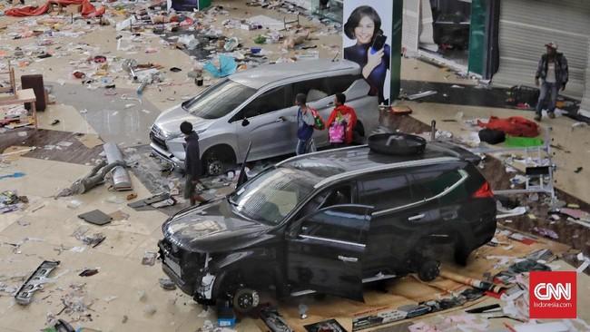 Sebuah mobil yang sehari-hari dipamerkan di Palu Grand Mall menjadi sasaran penjarahan warga. Onderdilnya, salah satunya ban, dipreteli, 2 Oktober 2018. (CNN Indonesia/Adhi Wicaksono)