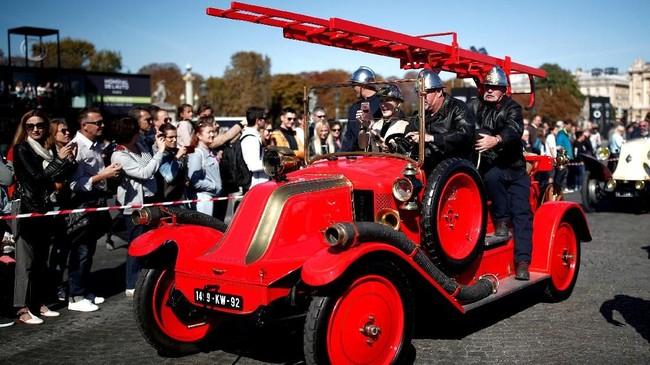 Peserta mengendarai kendaraan pemadam kebakaran berpartisipasi dalam parade Place de la Concorde bagian dari pameran otomotif Paris Motor Show ke-120 di Paris, Prancis. (REUTERS/Benoit Tessier)