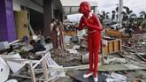 Warga mencari barang-barang yang bisa diambil di sebuah mal di Kota Palu pada 1 Oktober 2018. Pascagempa dan tsunami banyak warga mengambil bukan hanya barang kebutuhan, tetapi barang-barang lain yang tak terkait kebutuhan pokok di pusat-pusat perbelanjaan.(AFP PHOTO /AdekBerry)