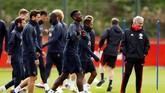 Jose Mourinho dan Paul Pogba berusaha menampakkan keceriaan meski tak saling tatap pada latihan di Carrington pada latihan sehari jelang Manchester United vs Valencia. (Reuters/Jason Cairnduff)