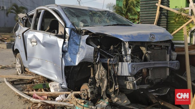 Orang-orang tidak bertangung jawab melepas sebagian komponen mobil yang menurut mereka masih bisa digunakan. Kejadian ini di sekitar Palu Grand Mall, Palu, Sulawesi Tengah, Rabu, 3 Oktober 2018. (CNN Indonesia/Adhi Wicaksono)