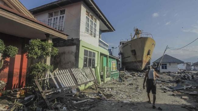 Warga melintas di depan kapal Sabuk Nusantara 39 yang terdampar ke daratan akibat gempa dan tsunami di desa Wani, Pantai Barat Donggala, Sulawesi Tengah. (ANTARA FOTO/Muhammad Adimaja)