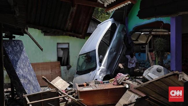 Sebuah mobil tampak tertumpuk berdiri di dinding rumah akibat terjangan tsunami. (CNNIndonesia/Adhi Wicaksono)