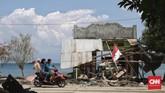 Tiga orang warga berboncengan di atas sebuah sepeda motor saat melintasi sebuah rumah warga yang hancur akibat terjangan tsunami di Desa Loli Pesua, Donggala, Sulawesi Tengah, 3 Oktober 2018. (CNNIndonesia/Adhi Wicaksono)