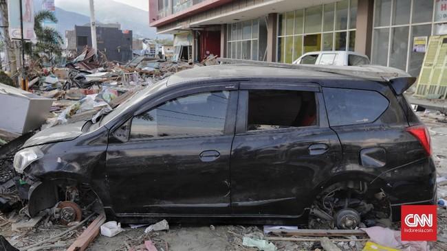 Mobil yang hancur terkena bencana gempa bumi berkekuatan 7,4 Magnitudo dipereteli pada bagian pelek di Palu, Sulawesi Tengah, Rabu, 3 Oktober 2018. (CNN Indonesia/Adhi Wicaksono)