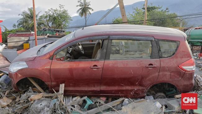 Para penjarah awalnya mencari bensin yang ada di dalam tanki kendaraan, tapi lama-lama setelah tidak ada bensin, mereka mulai mengambil spare part yang bisa dilepas di Palu, Sulawesi Tengah, Rabu, 3 Oktober 2018. (CNN Indonesia/Adhi Wicaksono)