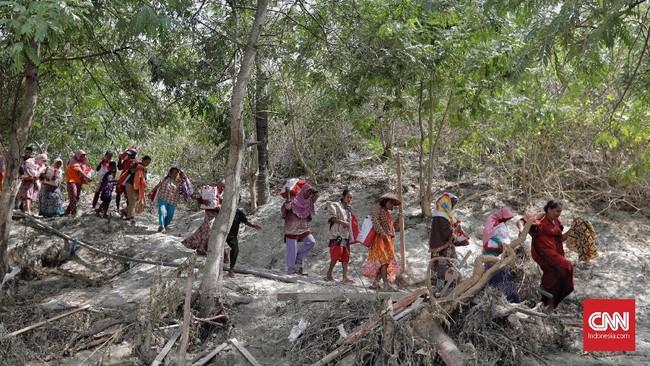 Warga korban gempa dan tsunami membawa bantuan dari Presiden RI Joko Widodo di Desa Loli Saluran, Donggala, Sulawesi Tengah, Rabu (3/10). (CNNIndonesia/Adhi Wicaksono)
