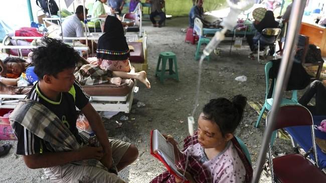 Seorang pasien korban gempa dan tsunami Sulteng memanfaatkan waktu membaca kitab suci di sebuah rumah sakit darurat di Kota Palu, 4 Oktober 2018. (REUTERS/Athit Perawongmetha)