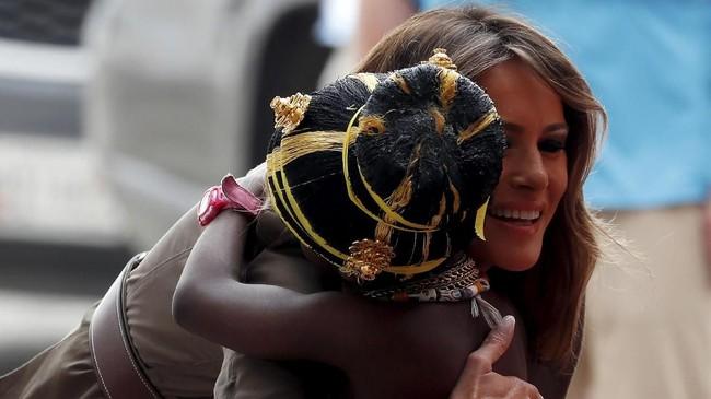 Sama seperti Michelle, Melania juga disambut dengan kehangatan warga Afrika, terutama anak-anak yang selalu minta digendong. (Reuters/Carlo Allegri)