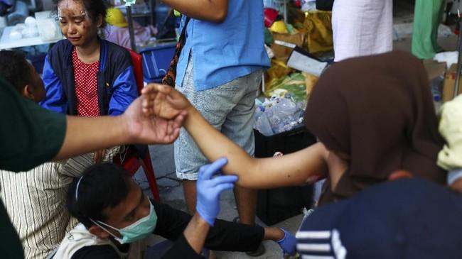 Tenaga medis melakukan pemeriksaan pada salah seorang korban gempa dan tsunami Sulawesi Tengah di rumah sakit di Kota Palu, 4 Oktober 2018. Pada hari yang sama, BNPB mendata jumlah korban jiwa telah mencapai 1.424 orang.(REUTERS/Athit Perawongmetha)