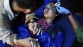Seorang pria menggenggam tangan anaknya yang sedang mendapatkan perawatan tenaga medis di sebuah rumah sakit di Kota Palu pascagempa dan tsunami Sulteng. (REUTERS/Athit Perawongmetha)