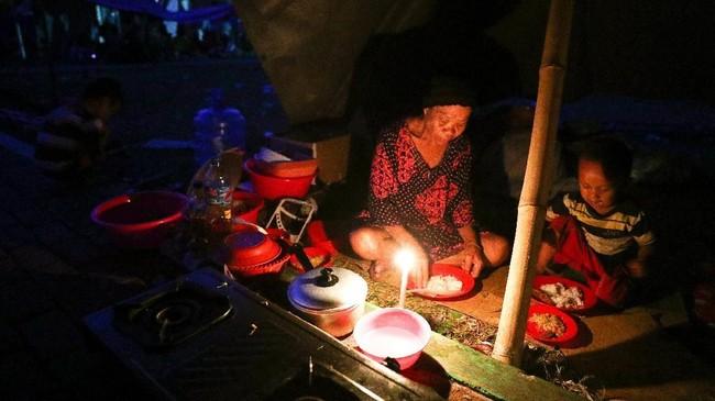 Masih banyak korban gempa dan tsunami Donggala dan Palu hanya menggunakan penerangan sekadarnya dari api lilin. (REUTERS/Athit Perawongmetha).