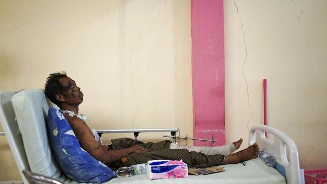 Seorang pasien korban gempa dan tsunami Sulteng, beristirahat dengan duduk di atas ranjang perawatan di sebuah rumah sakit di Kota Palu,4Oktober 2018. (REUTERS/Athit Perawongmetha)