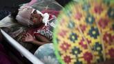 Seorang bocah laki-laki korban gempa dan tsunami Sulteng terbaring lemas di ranjang perawatan medis di sebuah rumah sakit lapangan di Kota Palu, 4 Oktober 2018. (REUTERS/Athit Perawongmetha)