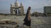 Seorang warga melintas di depan bangunan Masjid Arkham Babu Rahman yang hancur dan terhempas tsunami Palu. (AFP PHOTO/Mohd Rasfan)