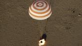 Turun menggunakan parasut oranye dan putih yang mengepul. Parasut ini touchdown dibantu roket di Dzhezkazgan, Kazakhstan. (Maxim Shipenkov/Pool via REUTERS)