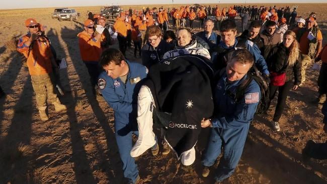 Personil darat membawa awak pesawat Ruang Angkasa Internasional (ISS) Ricky Arnold dari AS sesaat setelah pendaratan kapsul ruang angkasa Soyuz MS-08. (Maxim Shipenkov/Pool via REUTERS)