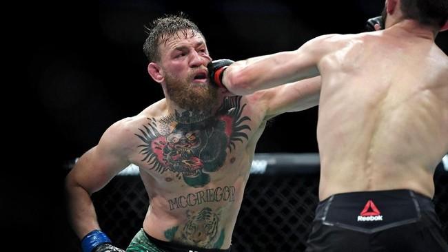 Conor McGregor berupaya melepaskan pukulan untuk merobohkan Khabib Nurmagomedov dalam sebuah partarungan atas. (Stephen R. Sylvanie-USA TODAY Sports)
