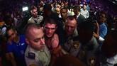 Khabib Nurmagomedov harus dikawal keluar dari ring setelah terlibat perkelahian di luar ring usai memenangi duel melawan Conor McGregor. Petarung berusia 30 tahun itu tercatat selalu meraih kemenangan dalam 27 pertarungan. (Harry How/Getty Images/AFP)
