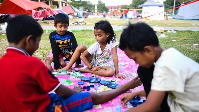 Anak-anak bermain di luar tenda di kamp sementara di Palu di Sulawesi Tengah. (AFP PHOTO / JEWEL SAMAD)