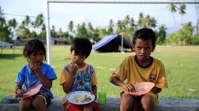 Anak-anak makan di luar tenda merekakarenaalasan keamanan setelah gempa di desa Biromaru di Sigi. (REUTERS/Beawiharta)
