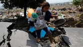 Seorang gadis membawa barang-barang berharga dari reruntuhan rumahnya setelah gempa bumi melanda kecamatan Balaroa di Palu. (REUTERS/Beawiharta)