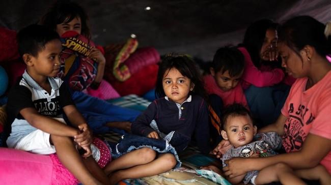 Keluarga yang terkena dampak gempa bumi dan tsunamiberada di tempat penampungan sementara di Donggala, Sulawesi Tengah. (REUTERS/Athit Perawongmetha)