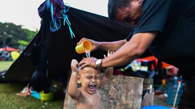 Seorang korban gempa memandikan putranya di luar kemahnya di sebuah kamp sementara di Palu. (AFP PHOTO / JEWEL SAMAD)