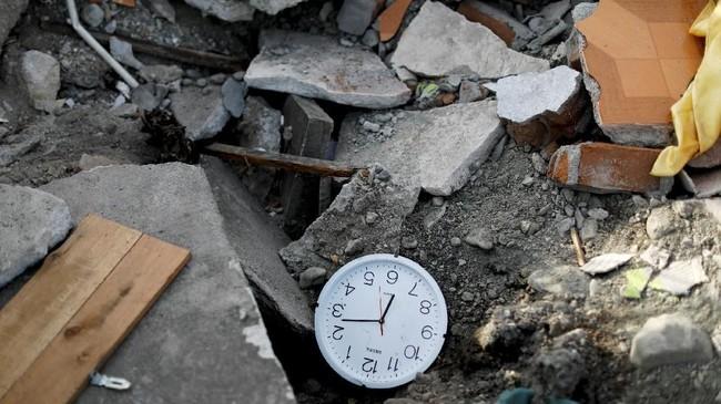 Jam dinding teronggok di puing-puing bangunan yang hancur diguncang gempa magnitudo 7,7. Diperkirakan lebih dari 5 ribu bangunan rusak setelah gempa dan tsunami menerjang. (REUTERS/Jorge Silva)