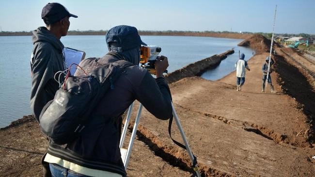 Petugas juru ukur tanah (Surveyor) melakukan pengukuran tanah dengan alat digital waterpass, diatas tanggul penahan lumpur Porong yang ambles di titik 67 Gempol Sari, Tanggulangin, Sidoarjo, Jawa Timur. (ANTARA FOTO/Umarul Faruq)