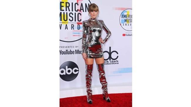 Taylor Swift terlihat sangat siap menguncang AMA 2018 dengan gaun metalik yang mirip mirror ball. Namun dia sukses membuat gaun mirror ball ini terlihat keren. (REUTERS/Mike Blake)
