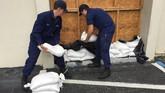 Penjaga pantai mempersiapkan kantong pasir di depan pintu masuk stasiun pemadam kebakaran di Yankeetown, Florida (U.S. Coast Guard/Seaman Michael Clark/Handout via REUTERS)