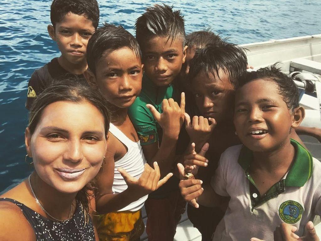 Foto: Tak hanya menunggangi ombak Mentawai, Maya juga berinteraksi dengan boca-bocah setempat. Begini keseruan mereka berpose bersama di depan kamera. (Instagram/@maya)