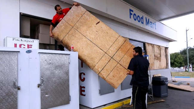 Pemilik toko p[un memasang penutup pada pintu dan jendela mereka sebagai antisipasi ketika badai menerjang (REUTERS/Jonathan Bachman)