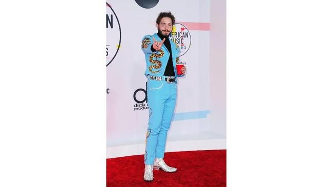 Post Maloneberani tampil beda dan di luar zona nyaman kaum pria dengan suit and tienya. Malone memilih jas dan pants biru cerah dengan detail bertuliskan namanya di pundak. (REUTERS/Mike Blake)