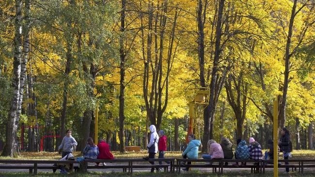 Musim gugur juga dipilih sebagai musim berwisata oleh penduduk dan turis di Minsk, Belarusia. Mereka bersantai di taman menikmati semilir angin dan meronanya warna pepohonan. (REUTERS/Vasily Fedosenko)