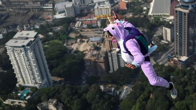 Seorang basejumper sedang melayang di Kuala Lumpur dengan kostum unicorn atau kuda terbang.