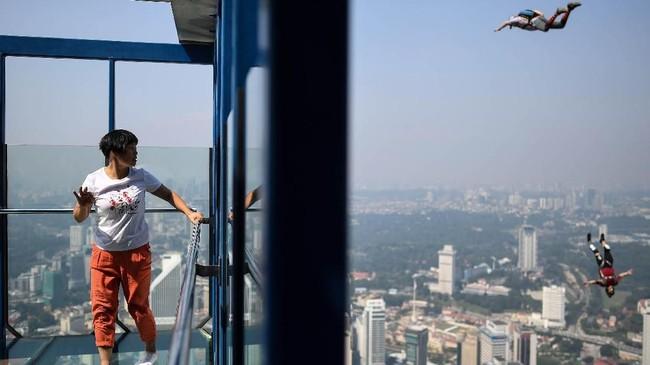 Seorang wisatawan yang sedang berada di menara Kuala Lumpur, menyaksikan para base jumper(sebutan bagi orang yang melakukan kegiatan base jumping) sedang beraksi.