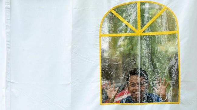 Penanganan dampak gempa Palu, Sulawesi Tengah masih terus berlanjut seiring dengan pemulihan trauma bagi anak-anak korban gempa. Seorang anak pengungsi gempa dan tsunami Palu mengintip dari jendela tenda pengungsian di halaman kantor RRI Palu, Sulawesi Tengah, Kamis (11/10). ANTARA FOTO/Yusran Uccang/aww/18.
