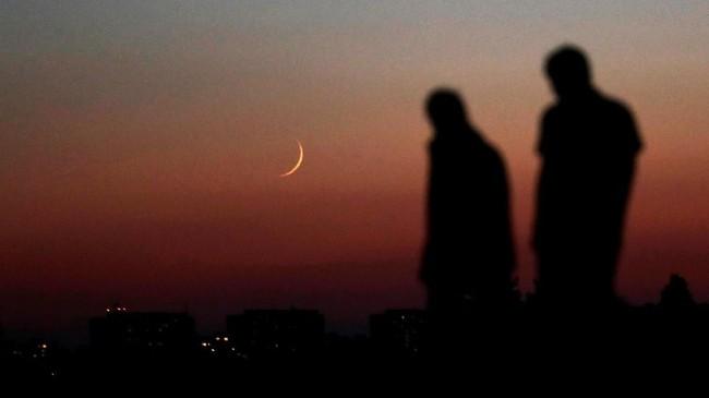 Orang-orang berjalan di bawah cahaya bulan yang baru saja muncul di langit kota Praha, Rep. Ceko. (Reuters/David W Cerny)