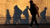Bayangan orang-orang yang berjalan di distrik bisnis Canary Wharf di London, Inggris, pada petang hari terpantul di suatu tembok. (Reuters/Russell Boyce)